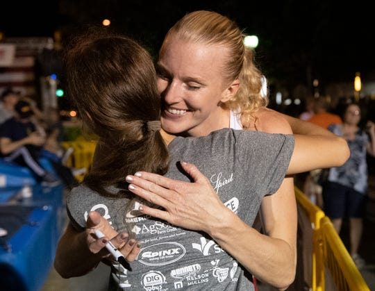 Sandi Morris hugs Ella Kulniszewski, 13, from Georgia, before signing her shirt after the Liberty Bridge Jump-Off on Main Street in Greenville Saturday, July 6, 2019.