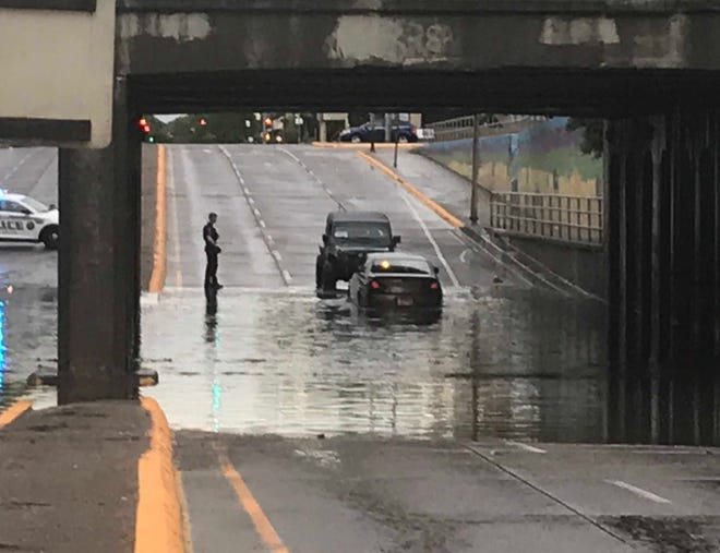 A Great Falls police officer watches as an SUV comes to the aid of a stranded motorist caught in Saturday's flash flood under the 1st Avenue North railroad overpass.