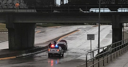 A Great Falls police officer approaches a disabled vehicle after the car tried to navigate the flooded railroad viaduct during Saturday's heavy rainfall.