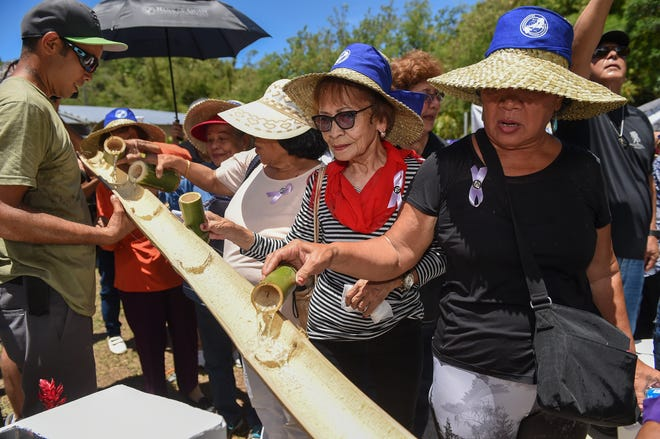 """War survivors participate in the traditional """"passing of the Bongbong and filling of the fountain"""" during the 75th Mañenggon Memorial Commemoration at Manengon Valley in Yona, July 7."""