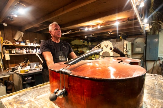 Chris Threlkeld-Wiegand of the Heartland String Bass Shop stands at a table where he restores a bass, Friday, June 28, 2019, at his home in Iowa City, Iowa.
