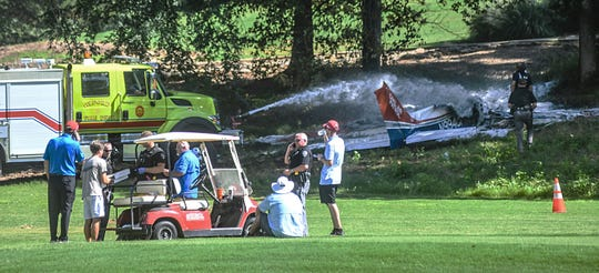 Emergency workers spray a plane which crashed on the 17th tee area of the Ole Miss Golf Course in Oxford , Miss., on Saturday, July 6, 2019.