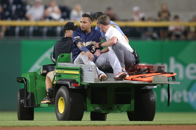 Brewers shortstop Orlando Arcia  is removed from the field after a collision with second baseman Keston Hiura in the eighth inning Saturday night.