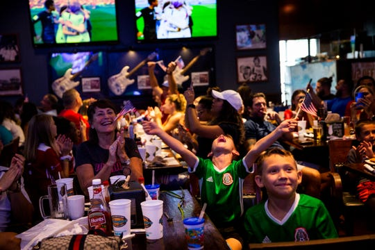 Cristian Gonzalez, center, waves American flags as he celebrates after watching the United States women's national soccer team beat the Netherlands 2-0 during a World Cup watch party at Bokamper's Sports Bar and Grill in Naples on Sunday, July 7, 2019.