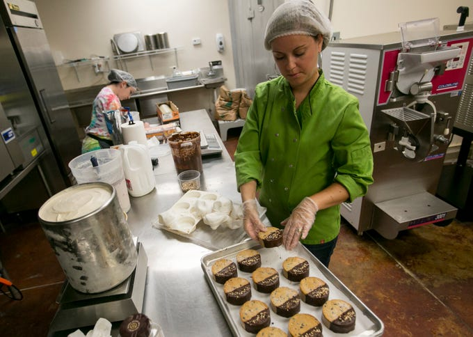 Kaat Pannekoecke dips her gelato cookie sandwiches in Belgian chocolate while filling an order for a client on Tuesday, July 2, 2019, in Fort Myers.