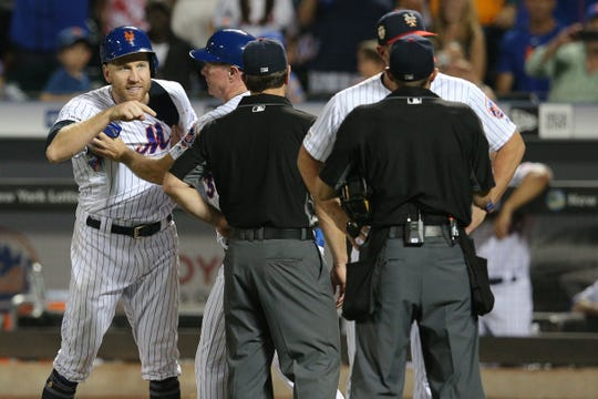 Jul 6, 2019; New York City, NY, USA; New York Mets third baseman Todd Frazier (21) is restrained by first base coach Glenn Sherlock (53) as he and New York Mets manager Mickey Callaway (36) argues with home plate umpire Tripp Gibson (73) after Frazier was hit by a pitch by Philadelphia Phillies starting pitcher Jake Arrieta (not pictured) during the fifth inning at Citi Field.