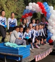 Members of the Ruidoso Gymnnastics Association participated in a 2018 holiday parade draped in red, white and blue.