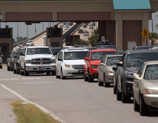 Traffic backs up heading to Pensacola Beach on July 7. Escambia County commissioners have agreed to go back to two designated SunPass transponder lanes and two cash toll lanes through Labor Day.