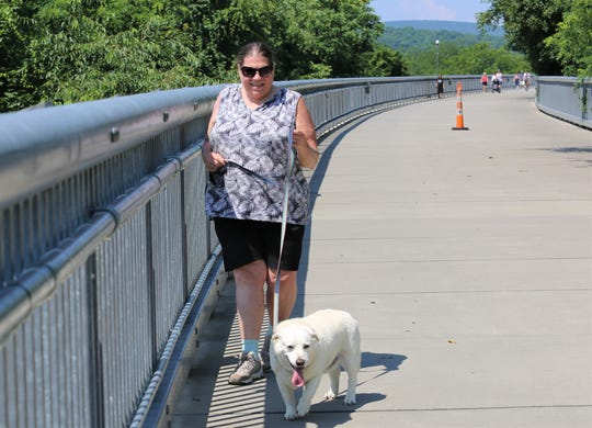 Darlene Hargrove and her dog Owney make their way toward the Poughkeepsie entrance of the Walkway Over the Hudson on Sunday, July 7, 2019.