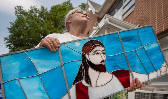 "Peggy Myers, of Ehrhart Glass, walks a panel to the scaffolding at Salem United Church of Christ in Jacobus for the latest three-window set titled ""Jesus Calling Disciples,"" which illustrates Mark 1:17 - ""Follow Me, and I will make you become fishers of men."""