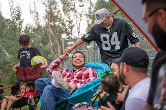 Jesse Duron, seated, greets a relative during a Lee Martinez family reunion at the Farm at Lee Martinez Park on Saturday, July 6, 2019, in Fort Collins, Colo.