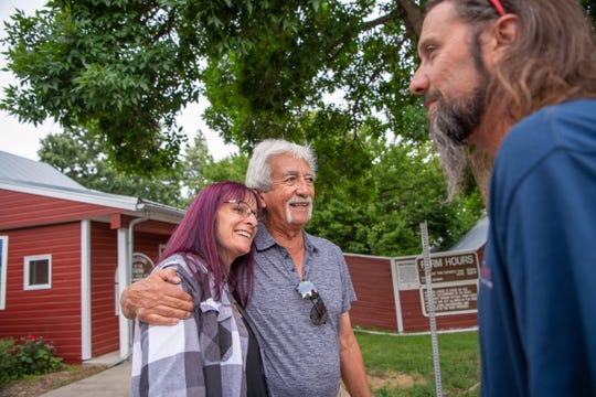 Philip Martinez gives Michelle Vornholt a hug as Bryon Vornholt looks on during a Lee Martinez family reunion at the Farm at Lee Martinez Park on Saturday, July 6, 2019, in Fort Collins, Colo.