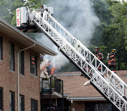 Yonkers firefighters work to stop the advancing fire in the cockloft at 50 Gateway Road during a 4-alarm fire, July 7, 2019.