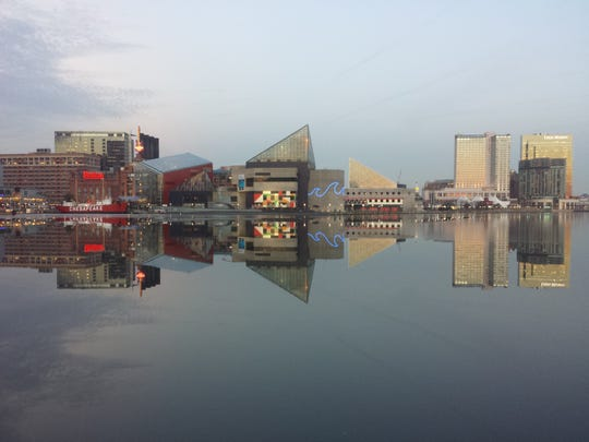 The skyline of Baltimore, Maryland, is reflected in a still and icy Inner Harbor on January 31, 2014.