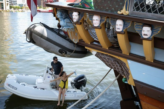 Vistors use a boat to take a closer look at the tall ship Kalmar Nyckel from Wilmington, where it is docked in the Inner Harbor as part of the Star Spangled Spectacular September 12, 2014 in Baltimore.