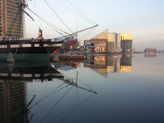 The USS Constellation (L) and the skyline of Baltimore, Maryland, USA are reflected in a still and icy Inner Harbor on January 31, 2014.