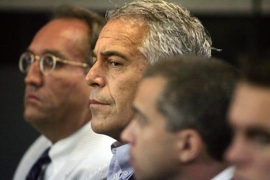 FILE - In this July 30, 2008 file photo, Jeffrey Epstein, center, is shown in custody in West Palm Beach, Fla. The wealthy financier and convicted sex offender has been arrested in New York on sex trafficking charges.