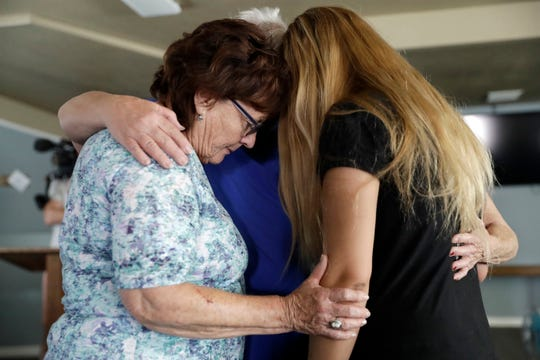 Alexandria Johnson, at right, whose home was damaged by an earthquake, prays with fellow congregants including Sara Smith, left, at the Christian Fellowship of Trona on July 7, 2019, in Trona, Calif.