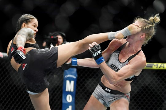 Amanda Nunes (red gloves) fights Holly Holm (blue gloves) at T-Mobile Arena.