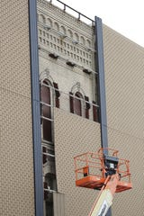The facade covering the original brick structure of the Gabriel Furniture building was removed piece by piece.