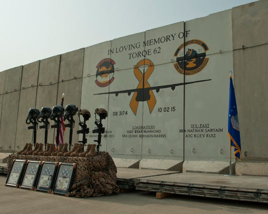 Battlefield crosses representing the six airmen lost during a C-130J crash, are placed in front of a mural in memory of TORQE 62, Bagram Airfield, Afghanistan, Oct. 2, 2016. A ceremony was held to remember and honor the live lost when TORQE 62 crash during takeoff at Jalalabad Airfield, Afghanistan, Oct. 2, 2015.