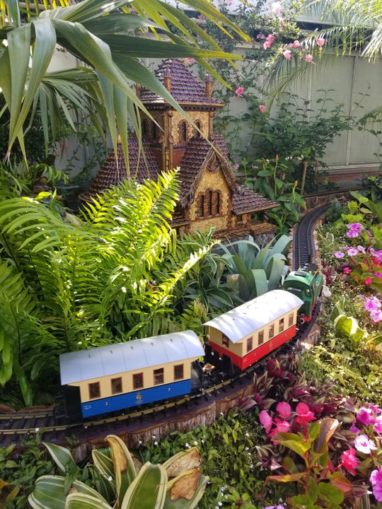 Biltmore Gardens Railway in the estate's Conservatory chugs past replicas of buildings on and near Biltmore Estate, like All Souls Cathedral.