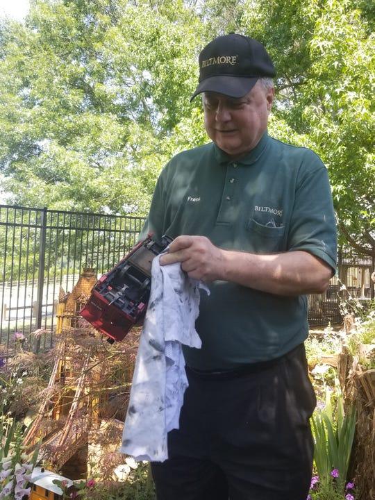Biltmore employee Frank Whatton cleans a train in the Antler Hill Village Biltmore Gardens Railway exhibit.