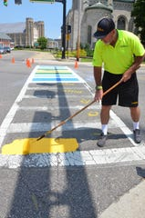 Brian McDavid, owner of Ace Parking Lot Striping in Kalamazoo, paints a rainbow-themed crosswalk at the Capital Avenue and Van Buren Street intersection on Monday, July 9, 2019.
