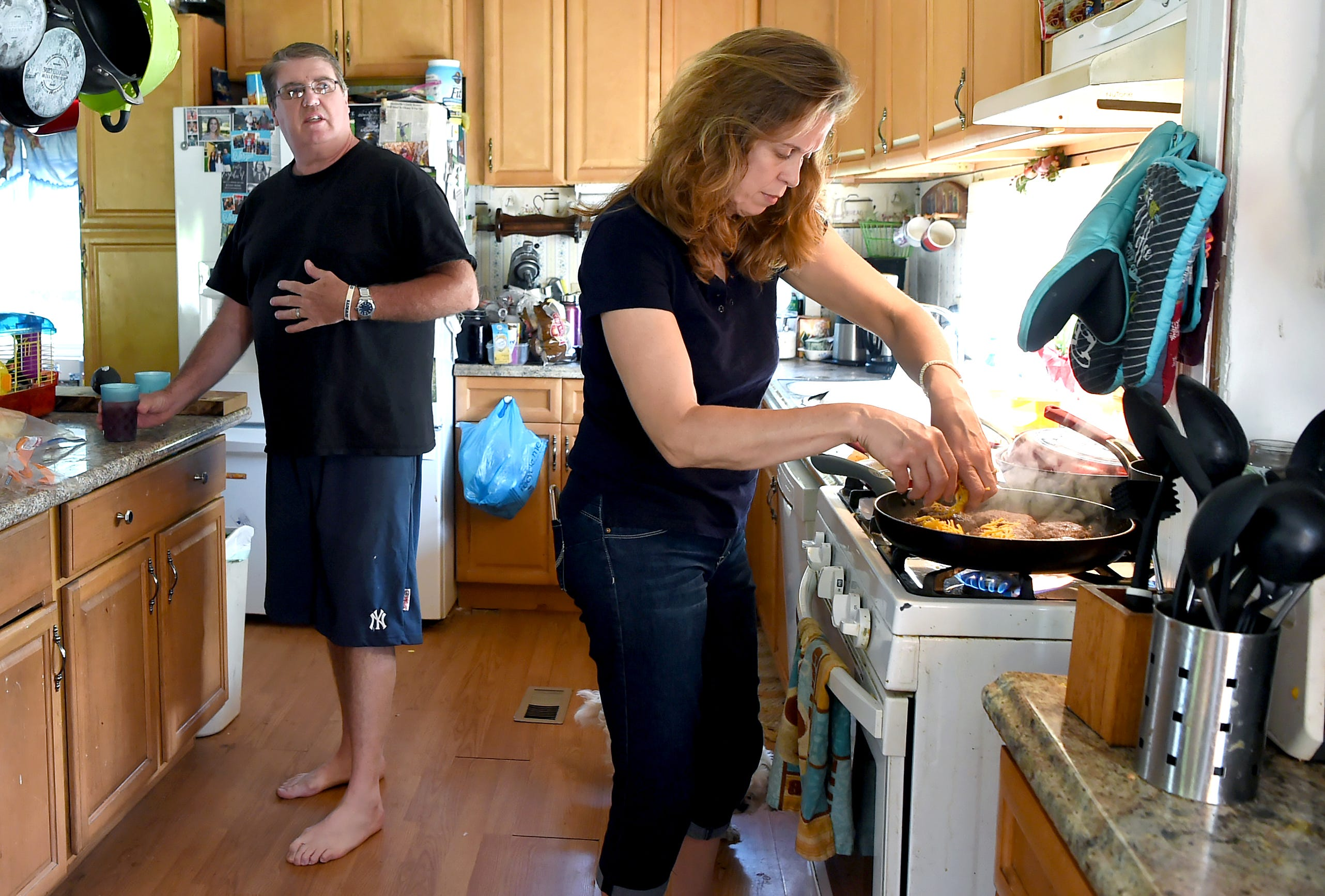 Sandy Brown, right, prepares hamburgers in the kitchen of the family's rural East Branch home while her husband looks on before daughter's Emily's high school graduation. With daughters requiring high calorie diets due to cystic fibrosis, the couple travels to Aldi's in Johnson City to stock up on large quantities of food.