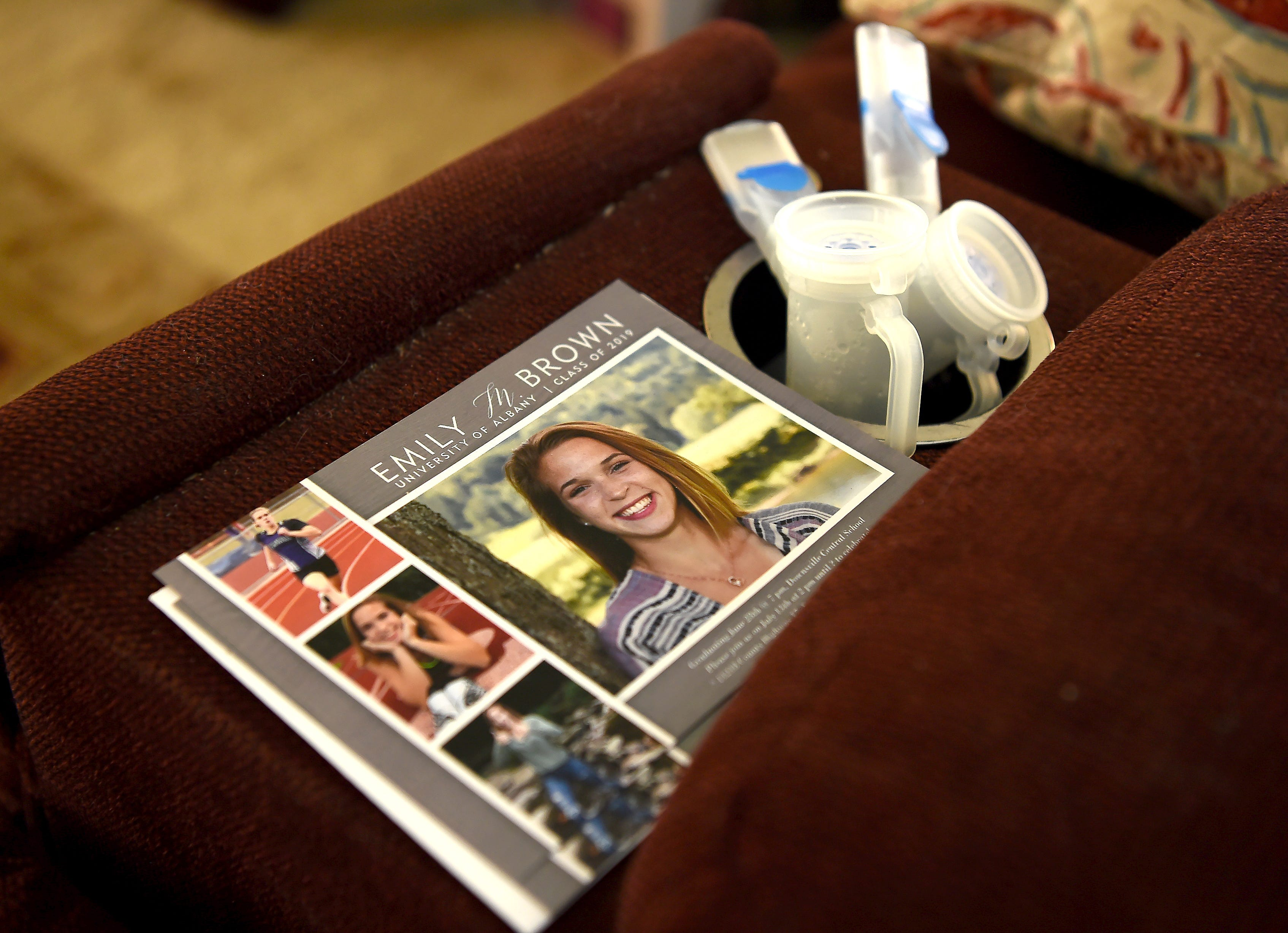Emily Brown's graduation announcement sits next to a medical device in her East Branch home. Emily, an athlete who was born with cystic fibrosis, will be attending University of Albany in the fall and running on the track team. Friday, June 28, 2019.