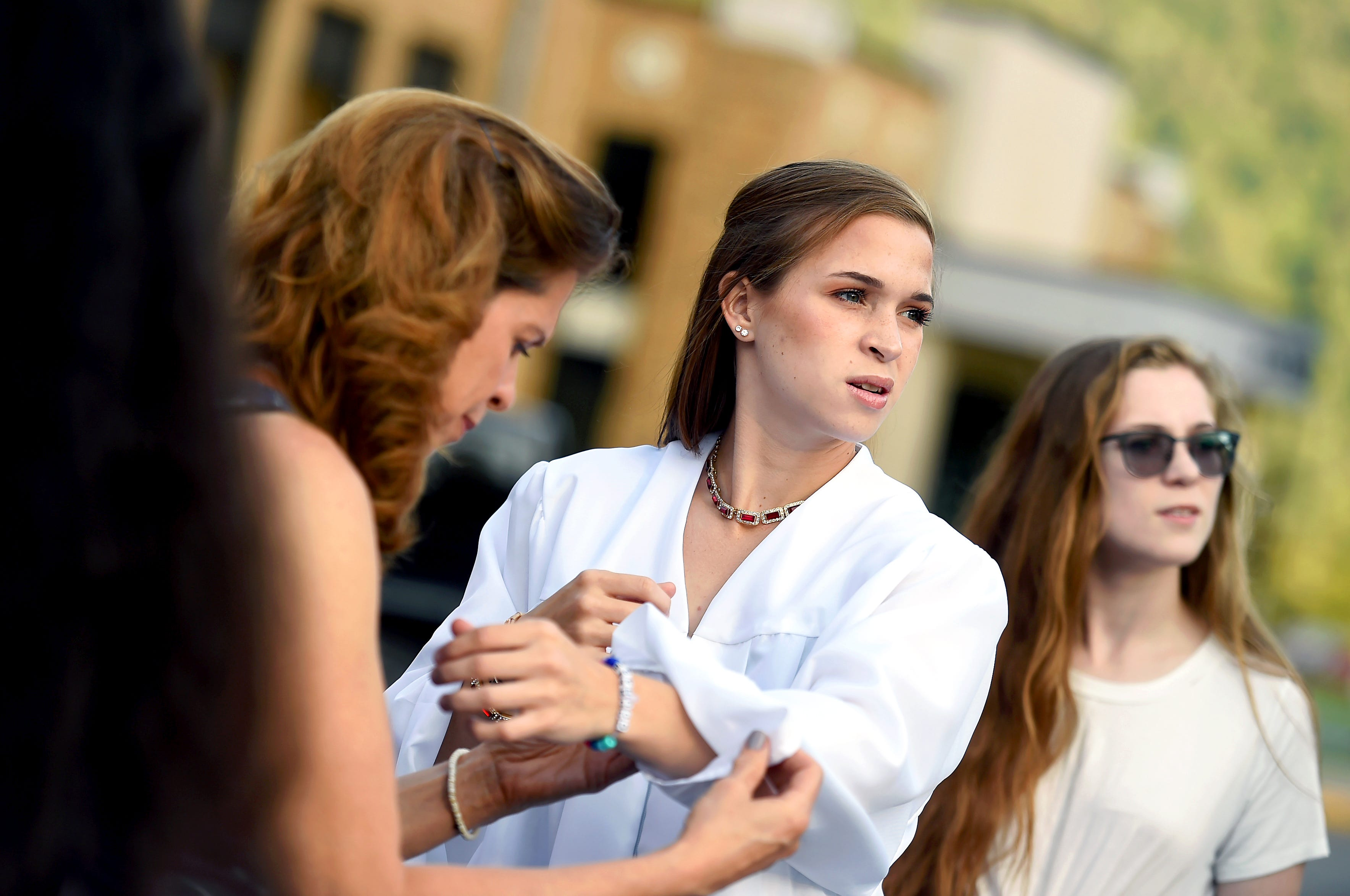 Emily Brown's mother, Sandy, helps her ready for graduation as her older sister Bethany, looks on before Emily's graduation from Downsville High School on Friday, June 28, 2019. As toddlers, both Emily and Bethany were diagnosed with cystic fibrosis.