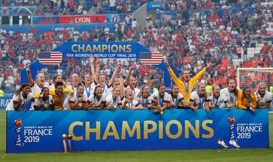United States players, including Satellite Beach's Ashlyn Harris, standing at right with arms extended, pose for a team photo after defeating the Netherlands in the championship match of the FIFA Women's World Cup France 2019 at Stade de Lyon.