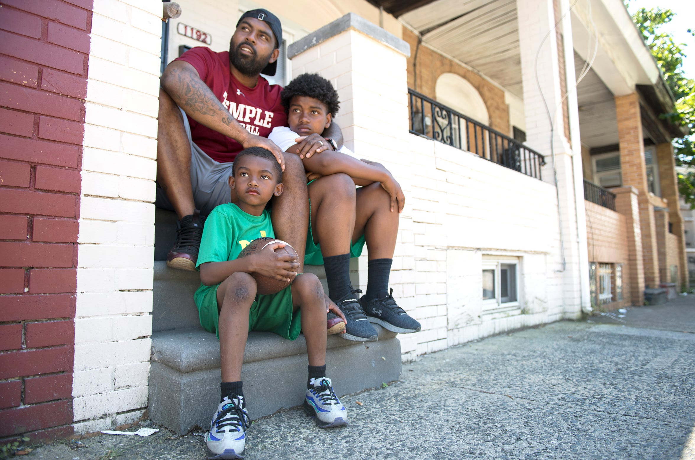 Fran Brown, top, a Camden native who became one of the best college football recruiters in the country and is now the co-defensive coordinator and cornerbacks coach at Temple University, sits with his sons Brayden, 7, left, and Frannie, 14, right, as they visit the home on Morton Street in Camden where Brown once lived.