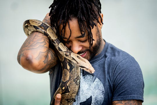 Ari White holds his snake Bam Bam, a red-tailed boa constrictor.