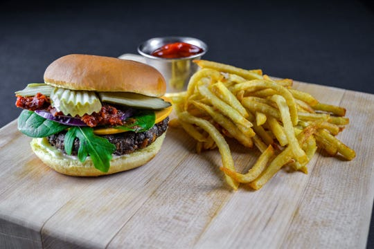 The Original Dirt Burger with tomato jam, house mustard seed pickles, aged cashew cheddar, shredded butter lettuce, red onion and herb mayo on a brioche bun.