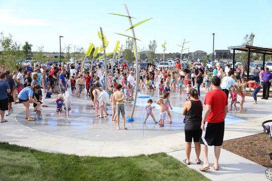 Children play at the splash pad at Fox Creek Park
