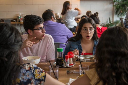 Joseph Abdaal and Adriana Abdaal, center, talk to their sisters Elayna Abdaal, far left, and Valia Abdaal, all of Commerce Township during dinner at Ima in Detroit, Friday, July 5, 2019.