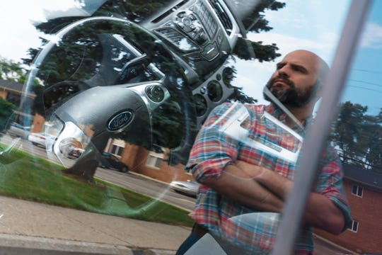 "Ryan Karczewski is reflected in the driver's side window of his 2014 Ford Focus SE outside of his apartment in Royal Oak on Friday, June 28, 2019. ""I absolutely feel that Ford has kind of left me out to dry with this,"" Karczewski said, who has had two clutch replacements on the vehicle since he purchased in 2014 and thinks he needs a third. ""This has pretty much been a nightmare and not what I expected when I bought a Ford product."""