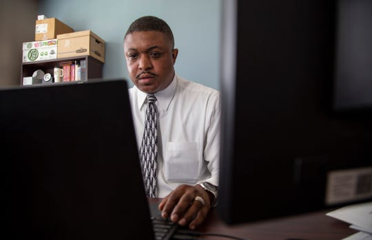 Niko Dawson, director of Flip the Script, works at his desk Wednesday, July 3, 2019.  Gov. Gretchen Whitmer's administration has proposed to cut $1.5 million in state funds to the prison diversion program.