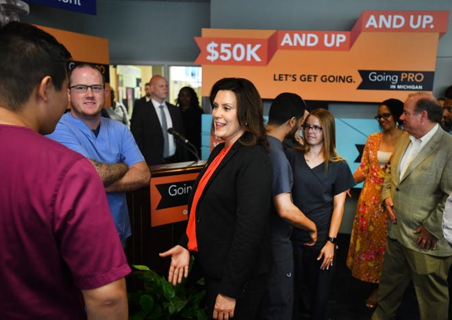 Gov. Gretchen Whitmer talks with Wayne County Community College students Kevin Yi and Aaron Hensley about the 'Going Pro' campaign highlighting occupations and industries with job opportunities  at Wayne County Community College in Detroit, Michigan on July 8, 2019. Mayor Mike Duggan is in the background, right.