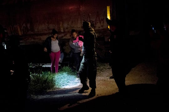 "A Mexican immigration agent and police detain migrants during a raid on the cargo train known as ""La Bestia"" in San Mateo, Chiapas state, Mexico, late Wednesday, June 26, 2019."