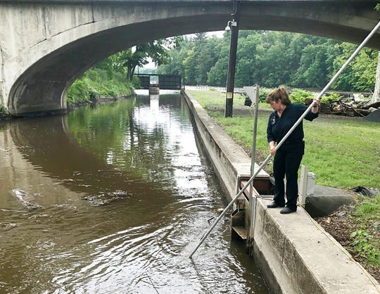 In this June 5, 2019 photo, Natural Power Group co-owner Sarah Bower-Terbush cleans debris from the canal that feeds the company's hydroelectric site in Wappingers Falls, N.Y. She and her husband sell renewable power to local customers from three hydroelectric sites they operate in the Hudson Valley. Customers say they like investing their money locally in clean power.