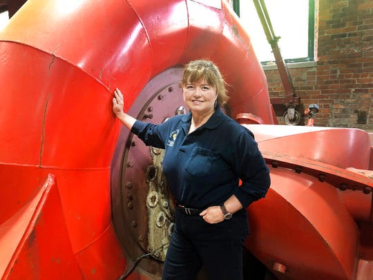 In this June 5, 2019 photo, Natural Power Group co-owner Sarah Bower-Terbush stands in front of a power turbine at the company's hydroelectric site in Wappingers Falls, N.Y.