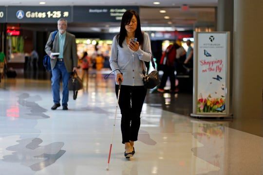 This June 9, 2019 photo shows Chieko Asakawa using the airport wayfinding app that she and her team at Carnegie Mellon University to navigate through Pittsburgh International Airside terminal in Imperial, Pa. before boarding a flight to Japan.