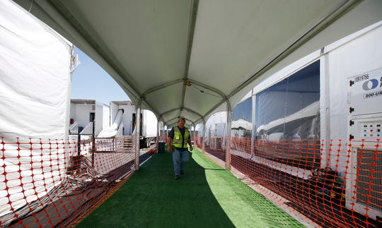 Workers put the finishing touches as the U.S. Border Patrol unveiled a new 500-person tent facility during a media tour Friday, June 28, 2019, in Yuma, Ariz.