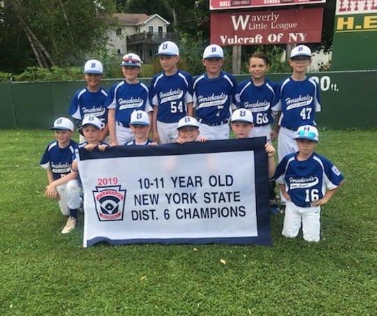 Horseheads players hold their championship banner after winning the District 6 9-11 division title with a 5-0 win over Big Flats on July 7, 2019 at Waverly.