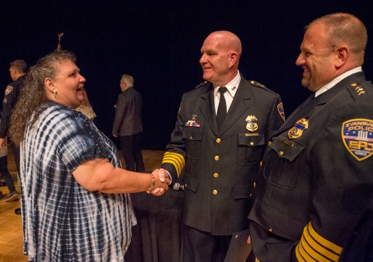 Civilian Award recipient Robin Simpson, left, thanks Assistant Chief Chris Pugh, center, and Chief Bill Bolin after the EPD Promotion, 
