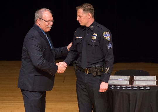 Retired EPD Lt. Dan DeYoung congratulates his son Peter DeYoung after pinning his sergeant badge during the EPD Promotion, 