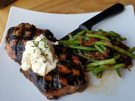 A grilled New York Strip with Boursin cheese and a side of bacon-enhanced green beans  from Bud's Rockin' Country Bar and Grill.
