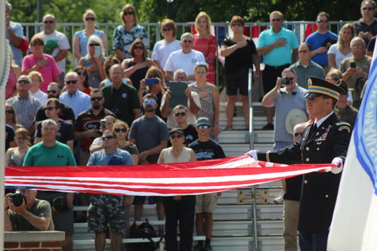 Crowds look on as the American flag is raised high above Camp Perry's Rodriguez Range as national  matches were declared underway following a first shot ceremony Monday.
